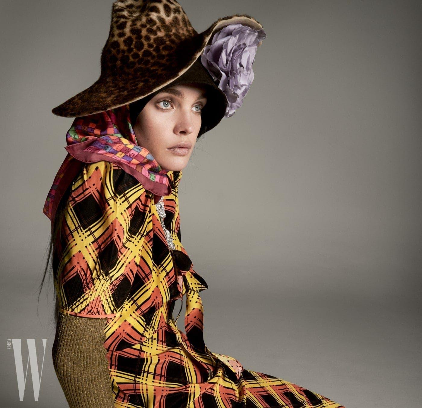 체크무늬 드레스는 Miu Miu, 터틀넥은 Tory Burch, 모자는 Patricia Underwood, 그 아래 커다란 코르사주 장식 모자는 Maison Michel, 알록달록한 스카프는 Hermes, 목걸이는 Chopard 제품.