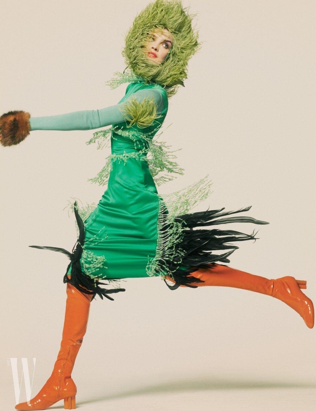 깃털 장식 드레스와 모자는 Prada, 터틀넥은 Salvatore Ferragamo, 오렌지색 부츠는 Louis Vuitton, 스톨은 Yves Salomon 제품.