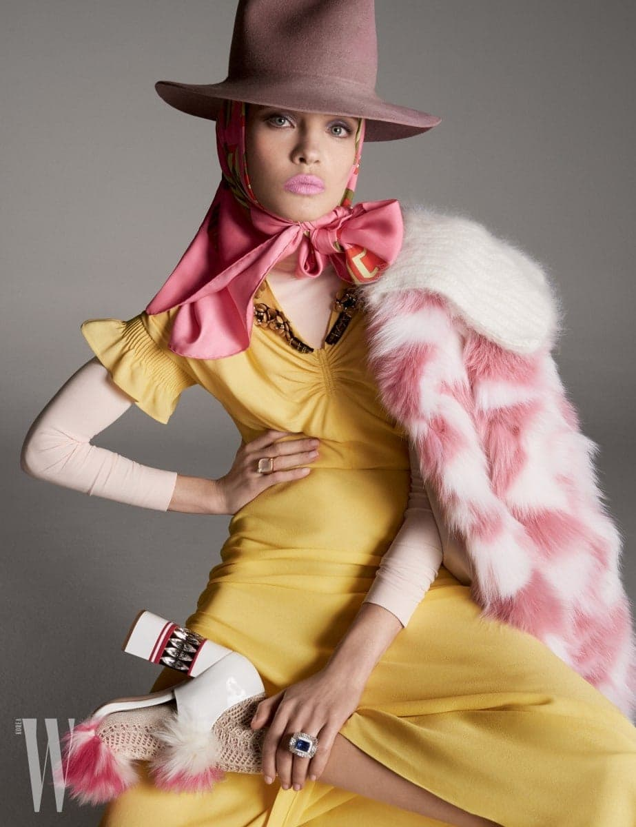 노란 드레스와 코트, 모피 장식 구두는 모두 Miu Miu, 터틀넥은 Tees by Tina, 페도라는 Preston & Olivia, 스카프는 Gucci, 오른손에 낀 반지는 Pomellato, 왼손에 낀 반지는 David Webb, 니트 양말은 Tabio 제품.