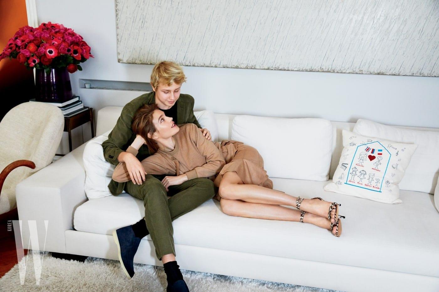 소파 위로 살짝 보이는 작품은 박서보의 그림이다. 루카스의 블레이저와 바지, 신발은 오피신 제너럴 제품. 나탈리아의 드레스와 구두는 지방시 제품.