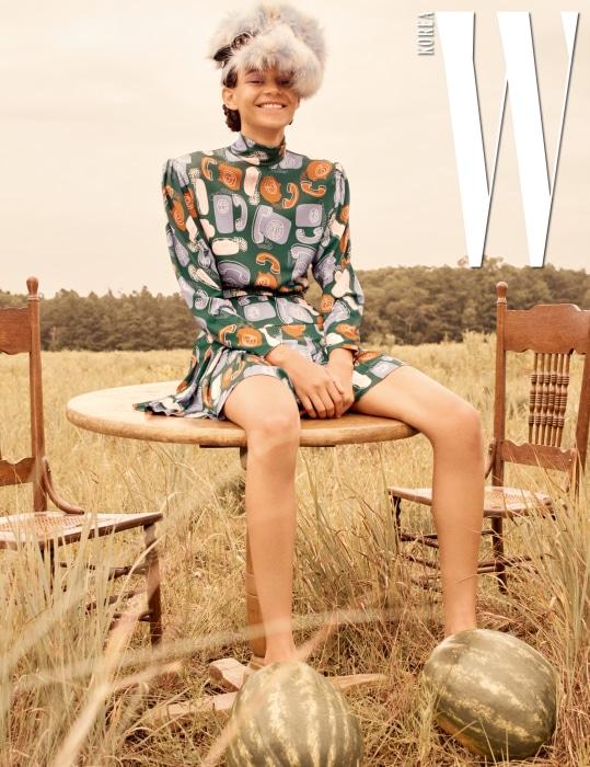 앙증맞은 전화기 프린트가 인상적인 레트로 무드의 드레스, 버클 장식 에코 퍼 모자는 Miu Miu 제품.