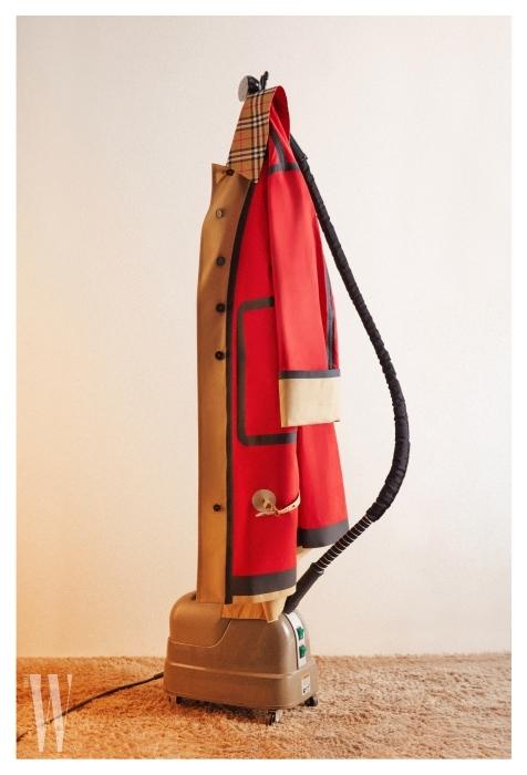 생동감 넘치는 붉은 톤의 컬러 블록이 신선함을 더하는 싱글 코트는 버버리 제품.