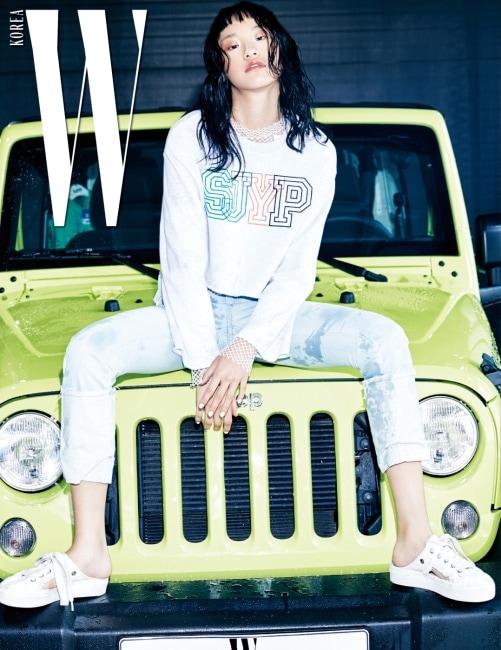 브랜드 로고가 장식된 크롭트 스웨트셔츠, 안에 겹쳐 입은 메시 톱, 롤업 데님 팬츠와 스니커즈 형태의 슬리퍼는 모두 SJYP 제품.