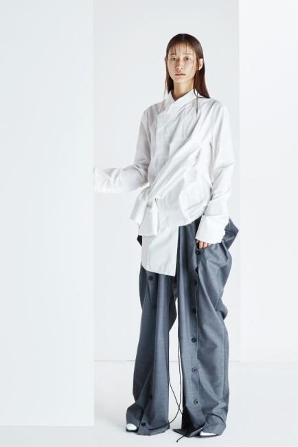해체주의적인 옷을 바라보는 새로운 시선이 담긴 셔츠, 독특한 실루엣의 버튼 장식 통 넓은 팬츠는 BMUET (TE) 제품.