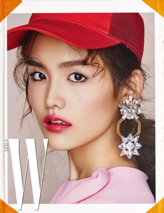 로맨틱한 핑크 드레스와 모자, 꽃 모티프의 크리스털이 연결된 볼드한 귀고리는 모두 Lucky Chouette 제품.