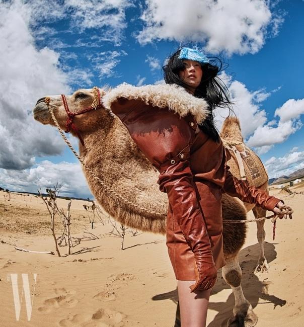 화보에 등장하는 비비드한 컬러 프린지 장식의 헤드피스는 모두 Q Millinery, 드라마틱한 실루엣이 돋보이는 가죽 드레스, 양털이 시어링된 슬리브 장갑, 사이하이 부츠는 모두 Saint Laurent by Anthony Vaccarello 제품
