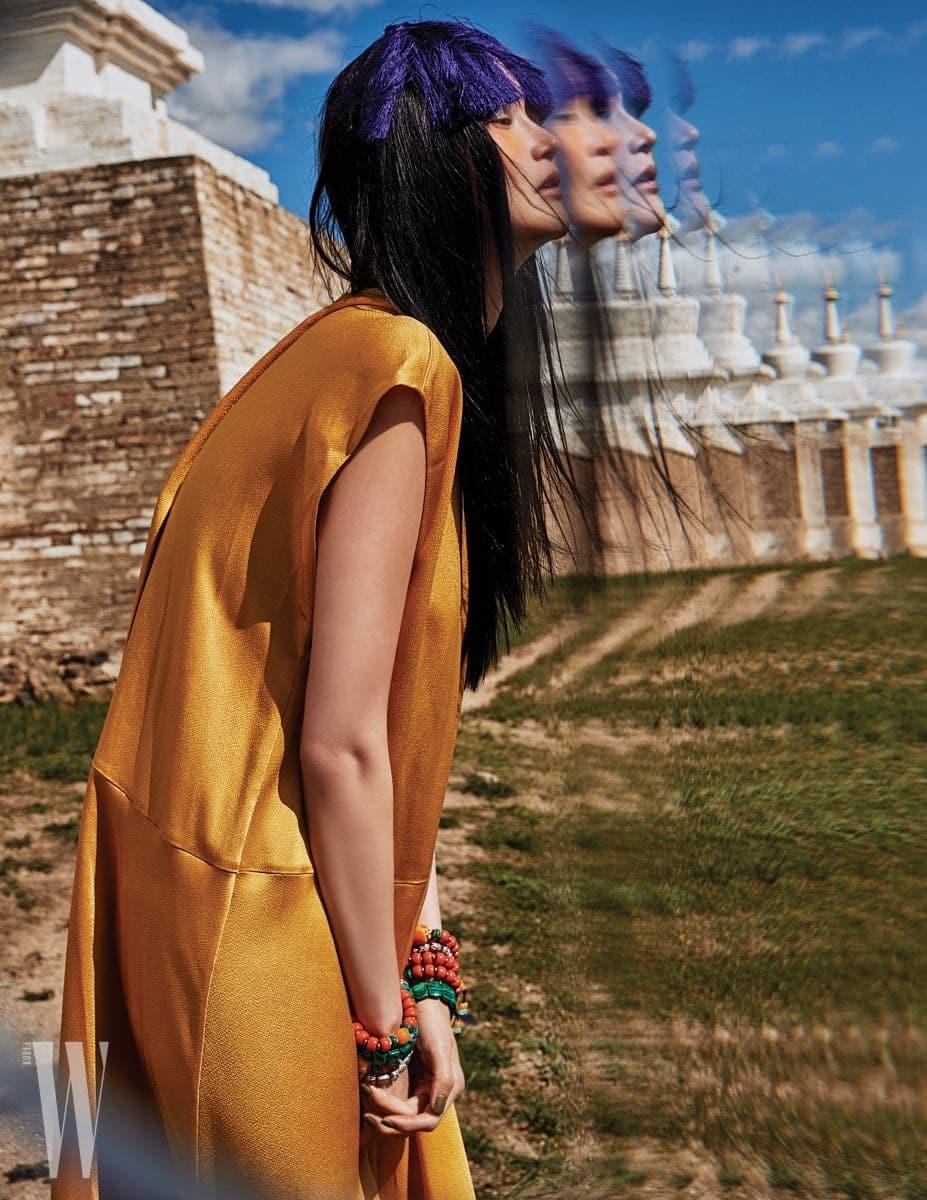 화보에 등장하는 비비드한 컬러 프린지 장식의 헤드피스는 모두 Q Millinery, 은은한 광택이 도는 노란색 실크 드레스는 Valentino 제품. 원석 장식 팔찌는 모두 에디터 소장품.