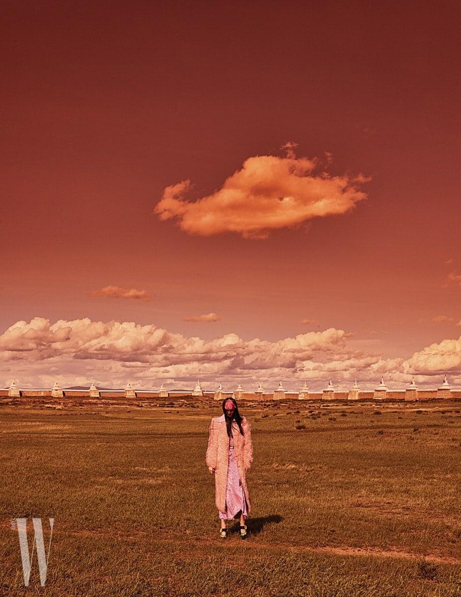 분홍빛 몽골리안 램스킨 퍼 롱코트, 레이스 브라, 크루넥 레이스 장식 보디슈트, 시퀸 장식의 롱스커트, 버클 장식 벨트는 모두 Nina Ricci, 정교한 비즈와 큼직한 버튼 장식이 돋보이는 메리제인 펌프스는 Prada 제품.