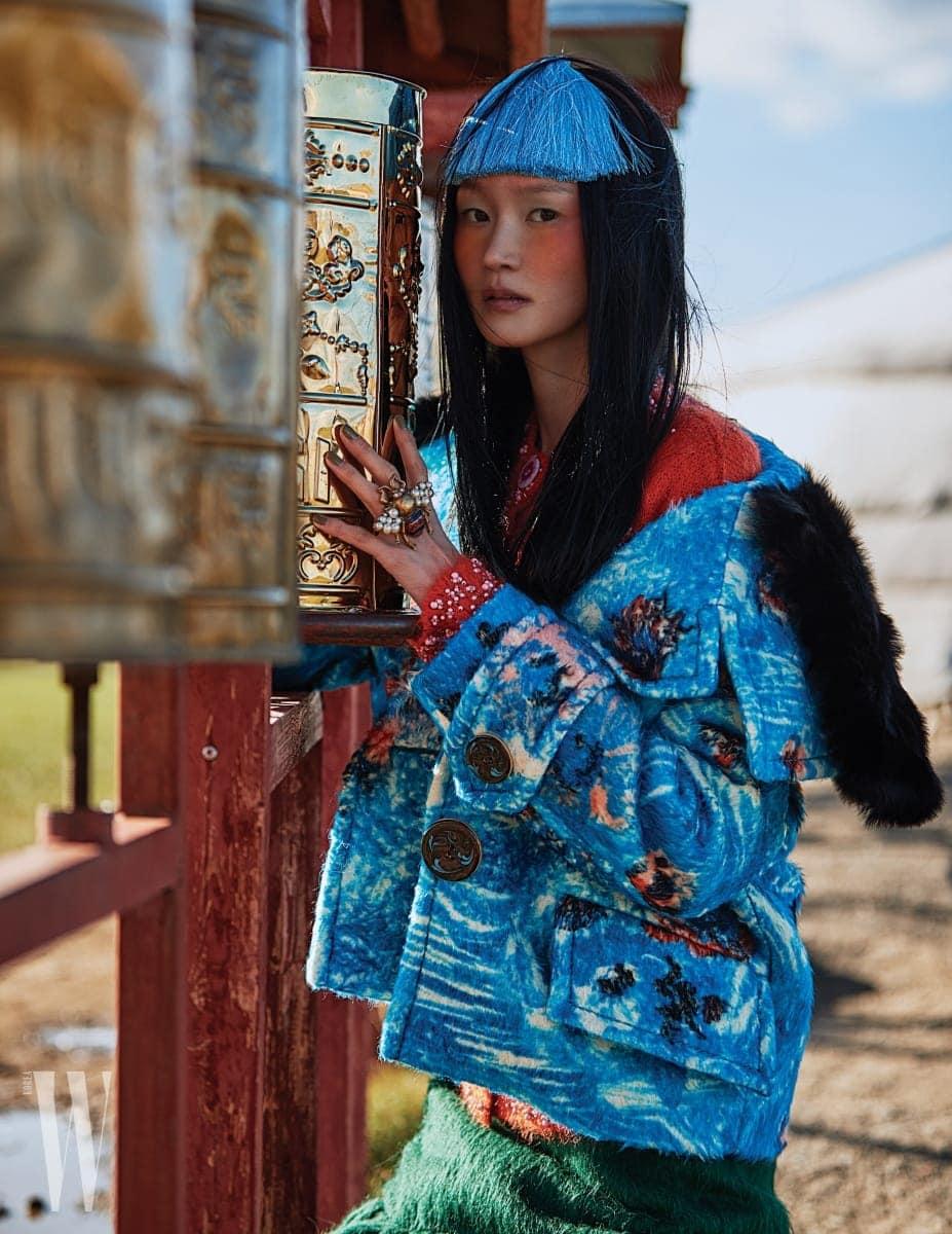 푸른색 알파카 코트, 비즈 장식의 오렌지색 모헤어 카디건, 실루엣이 여성스러운 초록색 알파카 스커트는 모두 Prada, 진주가 장식된 벌 모티프의 멀티 핑거 반지는 Gucci 제품.