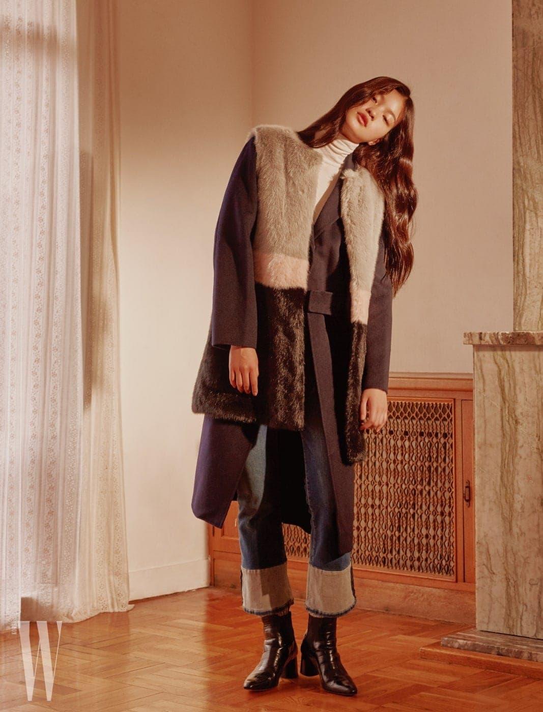 미니멀한 네이비 롱 코트와 컬러 배색이 돋보이는 페이크 퍼 베스트는 BLUEFIT, 부츠 컷의 롤업 진은 FRAME by BLUEFIT 제품.