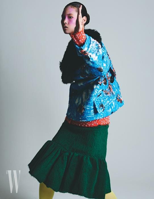 앨리스가 입은 추상적인 패턴의 코트, 안에 입은 비즈 장식 카디건, 초록색 머메이드 라인 스커트는 모두 Prada 제품.