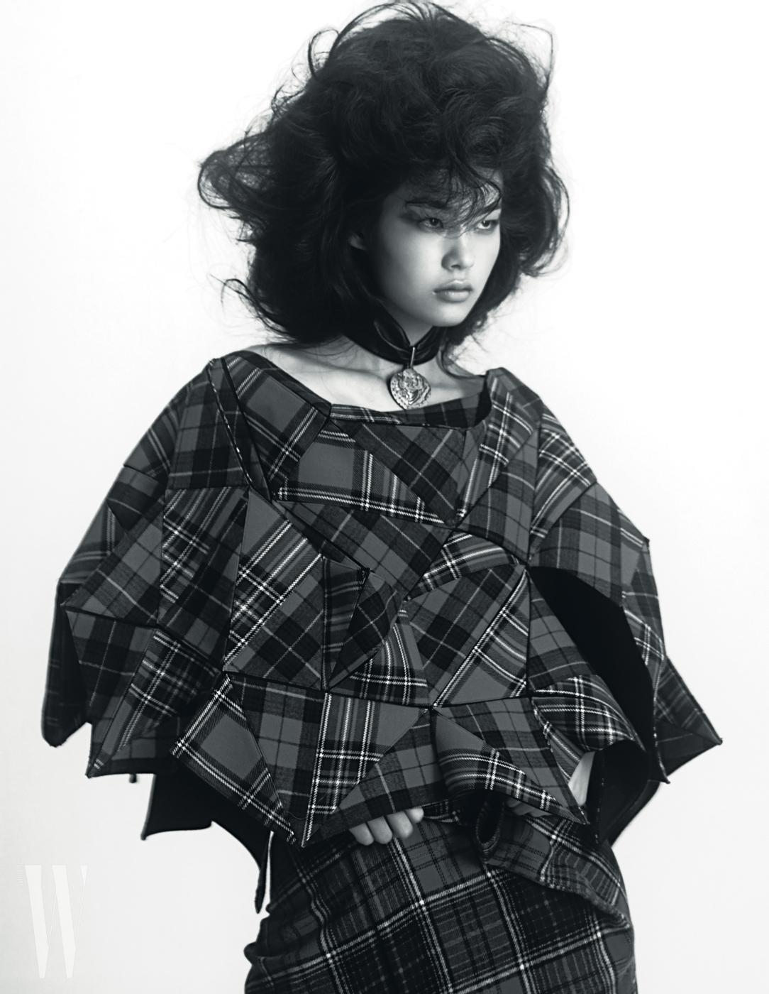 천예슬이 입은 오리가미 형태의 체크 케이프와 체크 스커트는 Junya Watanabe, 가부키 펜던트가 달린 초커는 Louis Vuitton 제품.