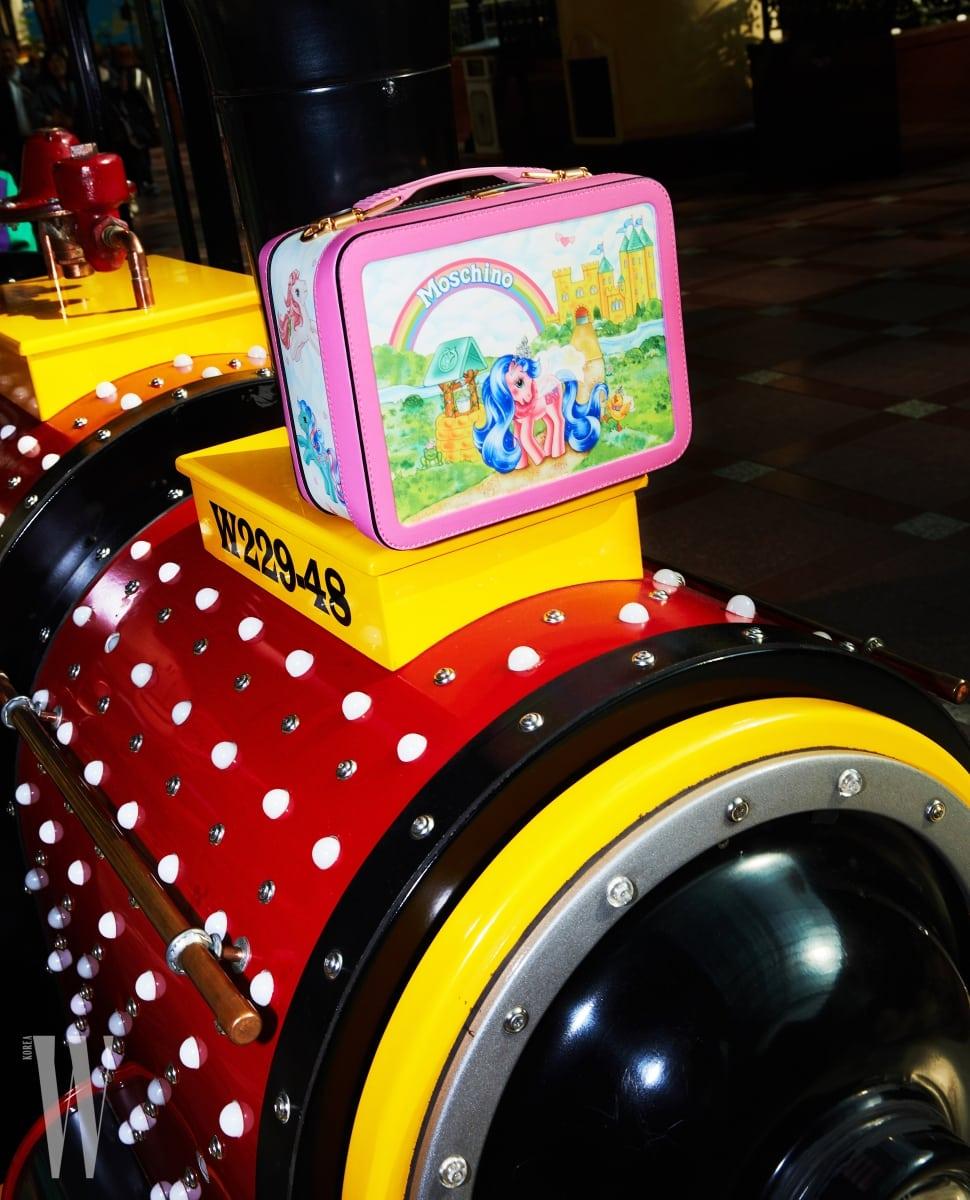 기차 위에 놓인 포니 캐릭터 사각 백은 모스키노 제품. 1백14만원.