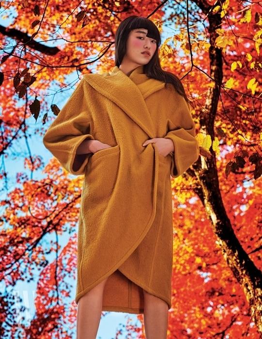 막스마라를 대표하는 클래식 카멜 코트. 1980년대의 특징적인 헴라인과 넓은 칼라, 여유로운 소매 실루엣이 눈길을 끈다.