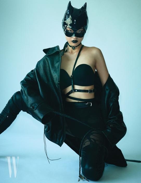 모델 천예슬이 입은 가죽 재킷과 타이츠는 Balenciaga, 안에 입은 브라톱은 Etam, 가죽 소재의 보디 서스펜더는 Zena Bayne by Net-A-Proter 제품. 캣우먼 마스크는 프롭 스타일리스트 제작 제품, 부츠는 에디터 소장품.