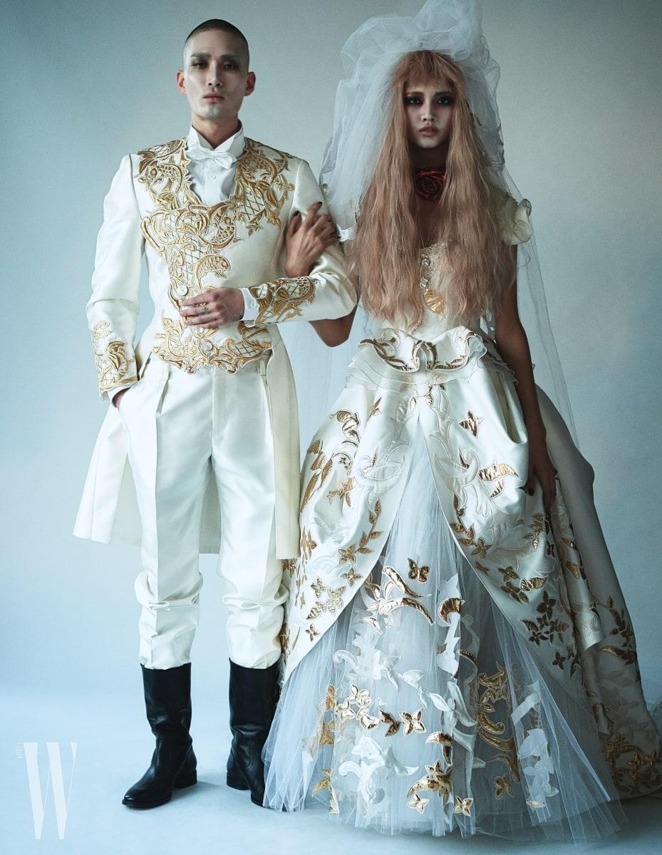 모델 노마 한이 입은 금색 자주 장식 웨딩 턱시도, 모델 이화가 입은 화려한 금색 자수 장식 웨딩드레스와 베일은 Andre Kim 제품. 노마 한이 신은 부츠는 Saint Laurent 제품.