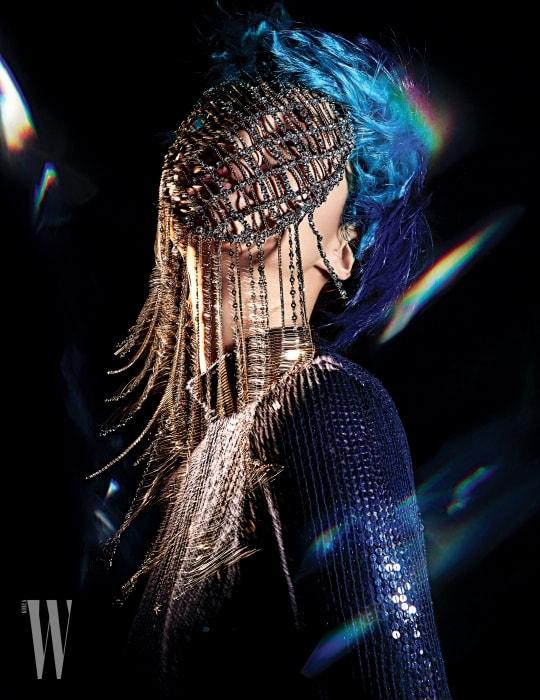 짙은 블루 색상의 스팽글 장식 터틀넥은 Vanessabruno, 크리스털 장식의 마스크는 Cocodemer by HAN 제품.