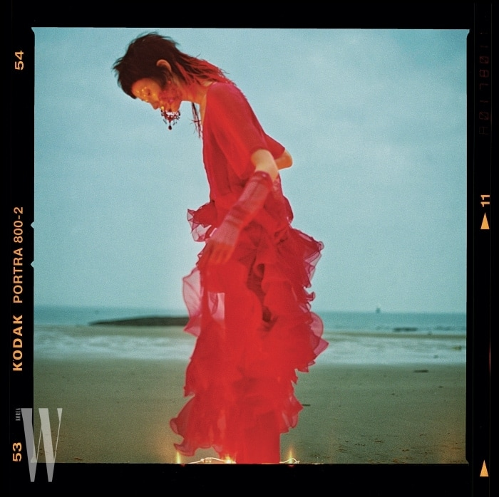 환상적인러플장식의붉은색드레스와샹들리에귀고리, 벨벳 팬츠, 시스루장갑은모두Givenchy 제품.