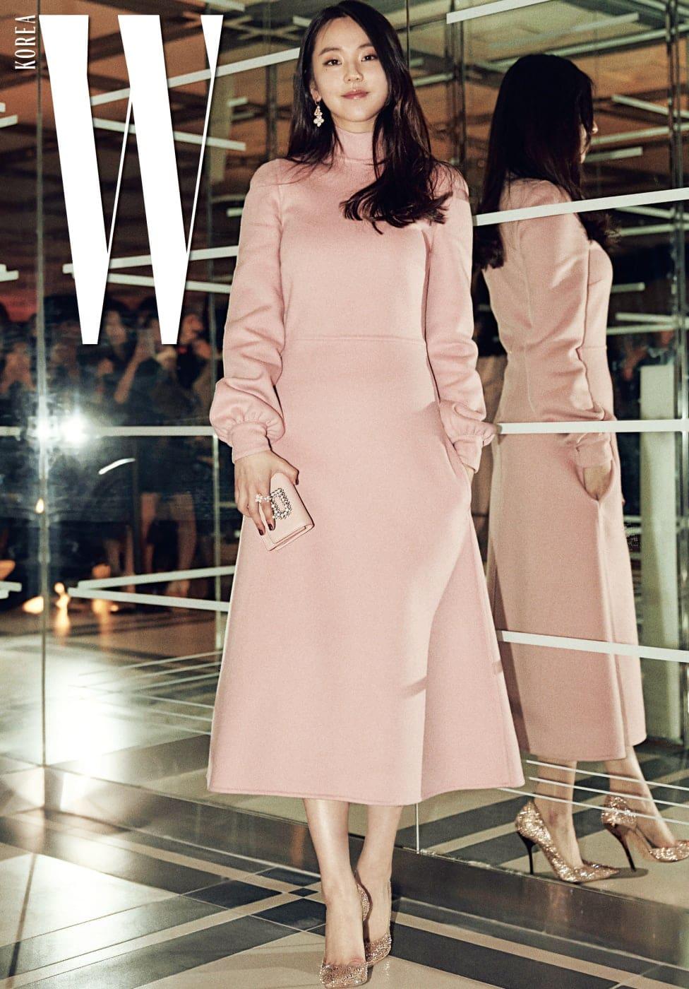 성숙하고 우아한 핑크빛 의상으로 거울 앞 포토존에 선 안소희. 여성스럽고 미니멀한 실루엣의 파스텔 핑크 드레스, 빛나는 R 로고 장식 미니 클러치는 Rochas제품. 스틸레토 힐은 Jimmy Choo 제품.