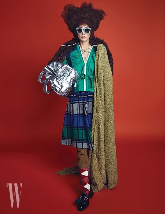 과장된 퍼 칼라 장식 패딩 재킷과 벨트, 니트 스커트, 진주 목걸이는 모두 Miu Miu, 어깨에 걸친 연두색 블랭킷은 Zara Home, 실버 패딩 가방은 Chanel, 줄무늬 선글라스는 Gentle Monster, 올리브색 니트 타이츠는 Hermes, 아가일 패턴 양말은 Burberry, 퍼와 주얼 장식 로퍼는 Prada 제품 .
