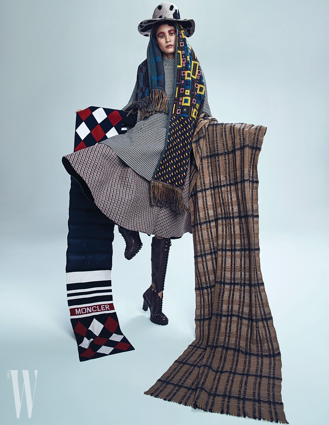케이프 형태의 코트는 Dior, 체크 패턴 스커트는 N˚21, 레이스업 부츠는 Valentino Garavani, 모자는 Shinjeo, 모자와 연출한 컬러 프린트 니트 머플러는 Isola Marras by Antonio Marras, 오른팔의 패딩 니트 목도리는 Moncler, 왼팔의 체크무늬 머플러는 Fabiana Fillippi 제품 .