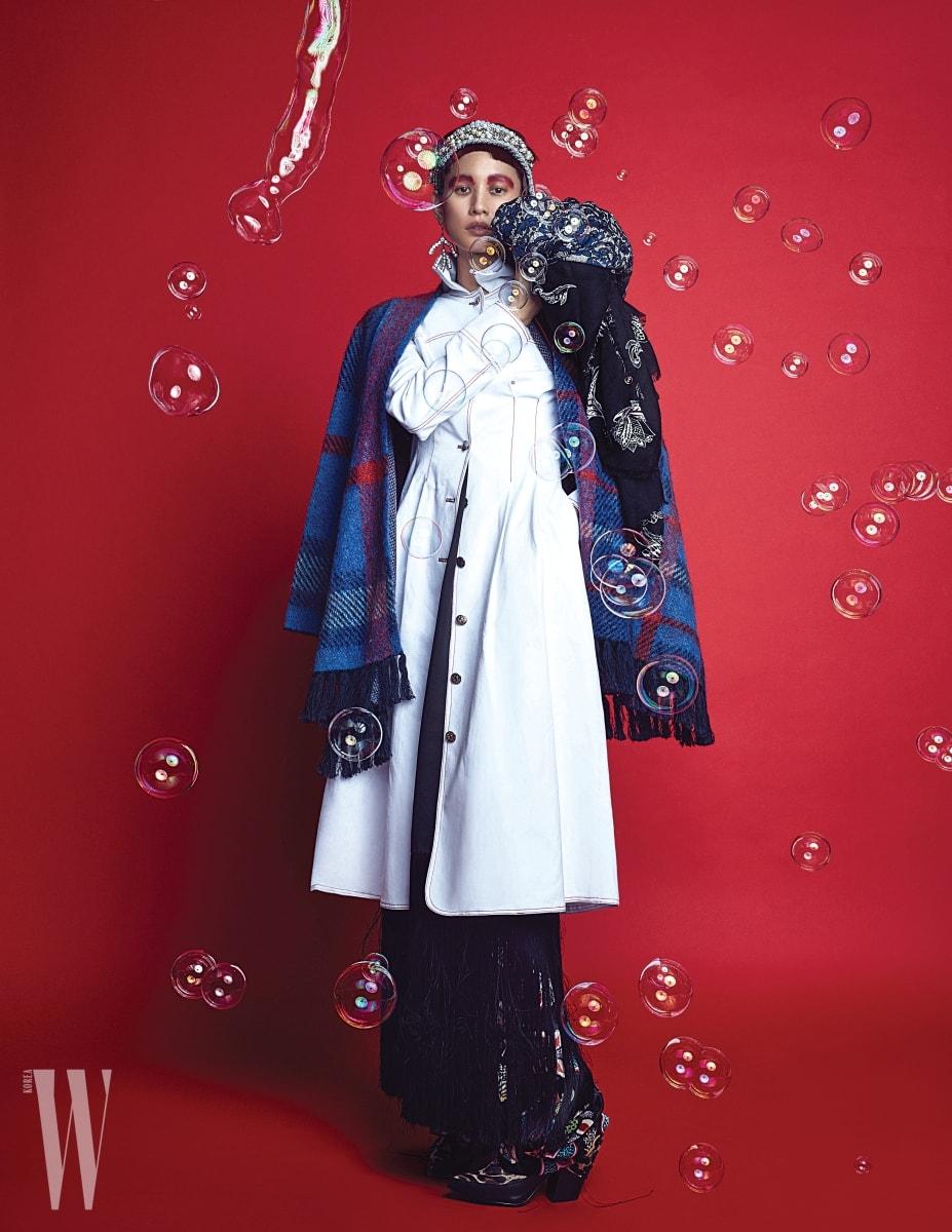 어깨에 두른 체크무늬 케이프는 Tommy Hilfiger, 흰색 아우터는 Fleamadonna, 프린지 장식 드레스와 귀고리는 Celine, 꽃무늬 벨벳 팬츠는 Valentino, 헤드밴드는 Chanel, 호피무늬 앵클 부츠, 왼쪽 어깨에 놓인 스카프는 모두 Louis Vuitton 제품 .