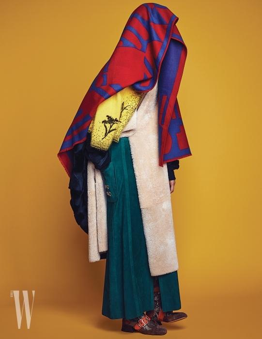 기하학적 무늬의 블랭킷은 Hermes, 코트는 Refur, 비즈 장식 노란색 앙고라 카디건은 Prada, 퍼 트리밍 네이비 케이프는 Georgio Armani, 녹색 스웨이드 스커트는 Hermes, 부츠는 Miu Miu 제품 .