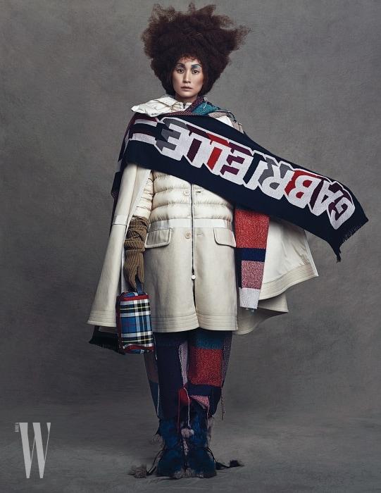 패딩 소재의 케이프 코트는 Moncler, 컬러 블록 니트 머플러와 팬츠는 Stella McCartney, 어깨에 두른 가브리엘 샤넬 머플러는 Chanel, 니트 장갑은 Michael Kors Collection, 체크무늬 미니 백은 Burberry, 퍼 부츠는 Prada 제품.