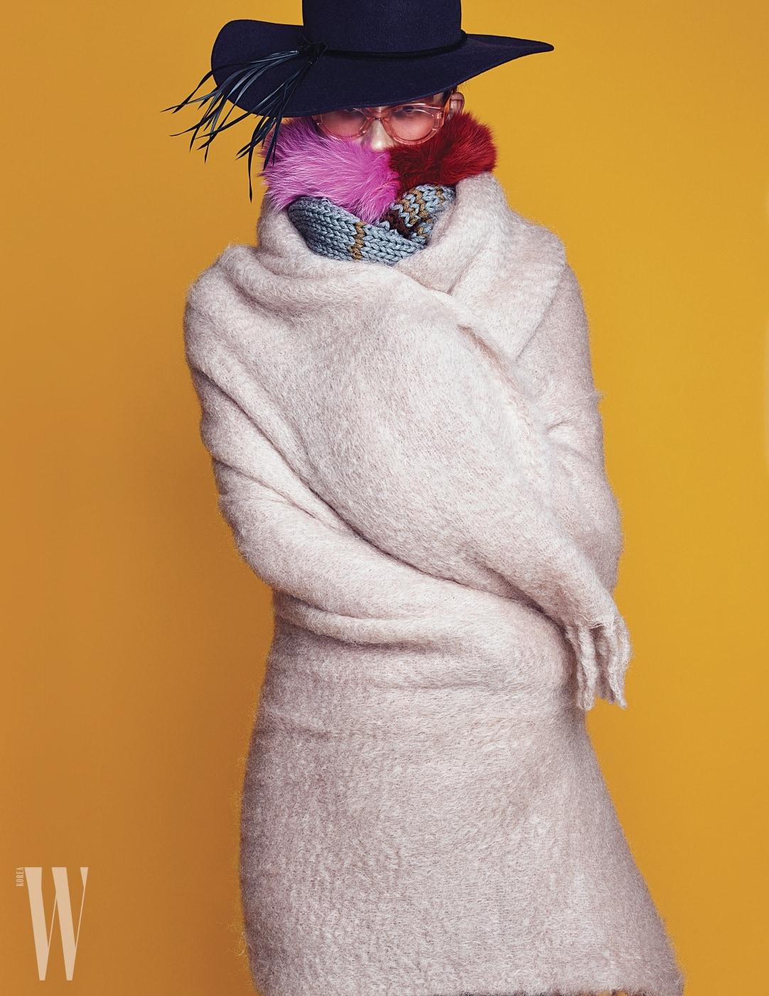 깃털 장식 모자는 Shinjeo, 투명한 핑크 선글라스는 Gentle Monster, 퍼 머플러는 Charlotte Simone by 10 Corso Como, 니트 머플러는 Prada, 모 소재의 블랭킷은 Zara Home 제품 .