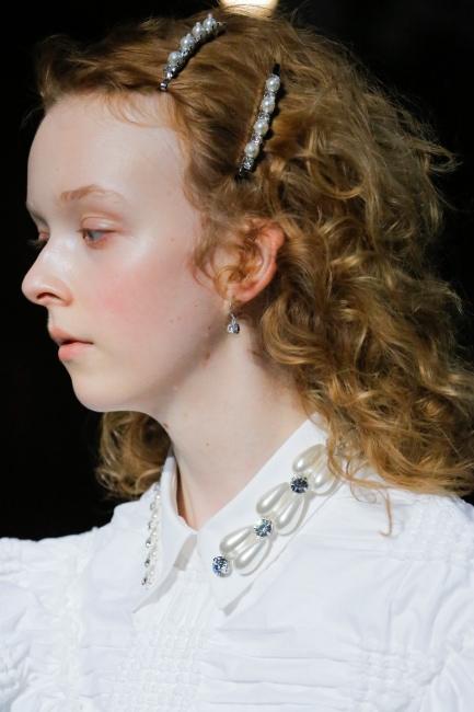 풍성한 컬리 헤어에 볼드한 진주 핀을 스타일링한 18SS Simone Rocha 컬렉션 룩.