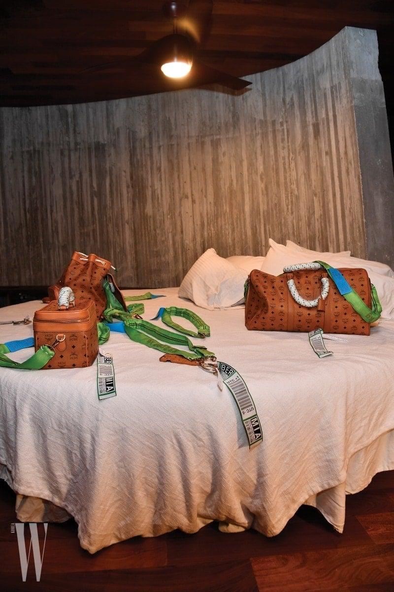 선 패스 하우스 방 안의 침대 위에 진열된 쾨니히 수버니어와 MCM의 한정판 컬래버레이션 아이템들.