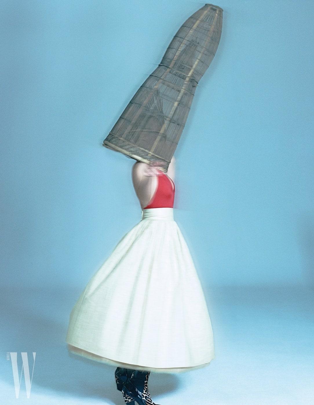 빨간색스윔슈트는Valentino, 한국고유의색과소재로 이루어진모시스커트는Jintaeok, 레오퍼드앵클부츠는 Louis Vuitton 제품. 머리에쓰고있는것은 어촌에서사용되던전통어망 .