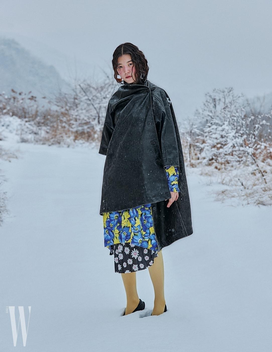 거친 워싱의 가죽 코트와 꽃무늬 원피스, 스타킹, 검은색 슈즈, 이어링은 모두 발렌시아가 제품. 코트와 스타킹, 이어링은 가격 미정, 원피스는 2백만원대, 슈즈는 1백만원대.