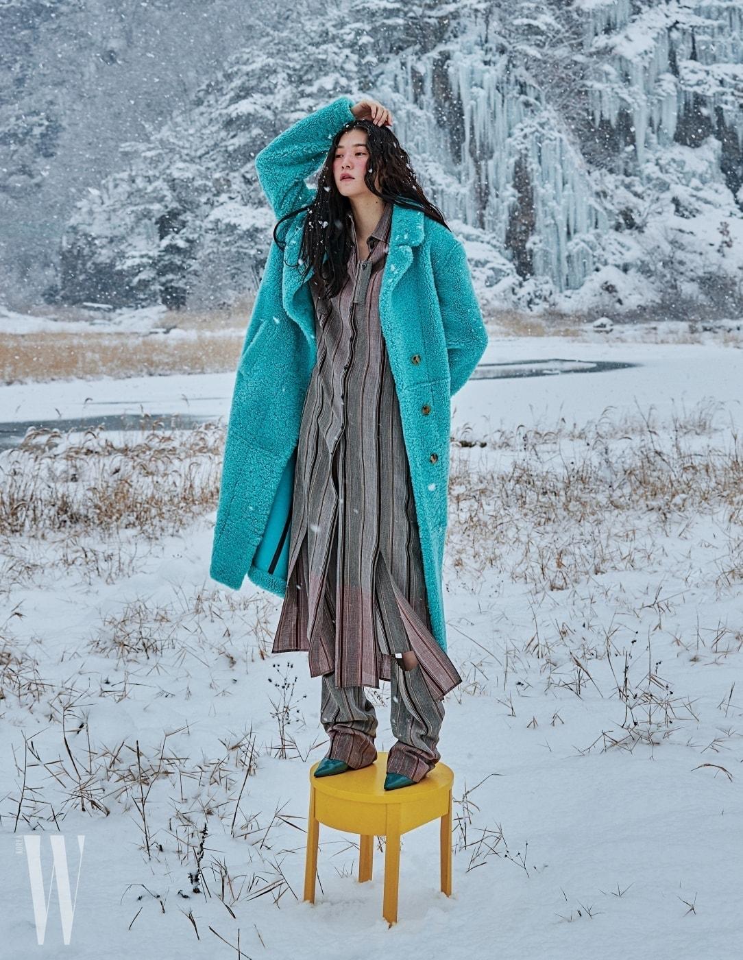시어링 소재의 푸른색 롱 코트는 버버리 제품. 8백50만원. 밑단 절개 장식이 독특한 스트라이프 패턴 롱 셔츠와 무릎에 절개가 있는 팬츠, 푸른색 펌프스는 모두 셀린 제품. 모두 가격 미정.