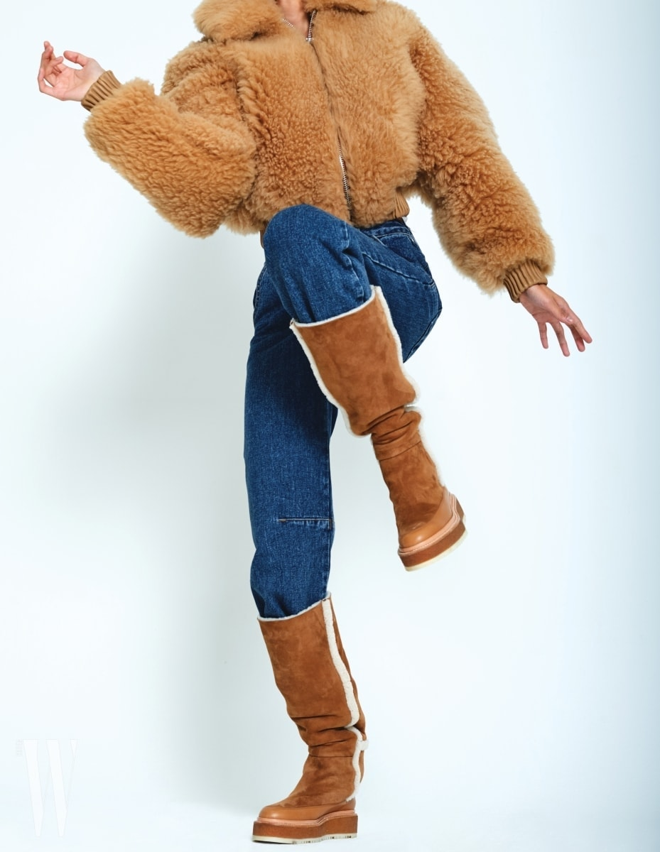 귀여운 양털 쇼트 점퍼는 아크네 스튜디오 제품. 3백57만원. 데님 팬츠는 로클 제품. 10만원대. 양털 트리밍 스웨이드 부츠는 에르메스 제품. 가격 미정.