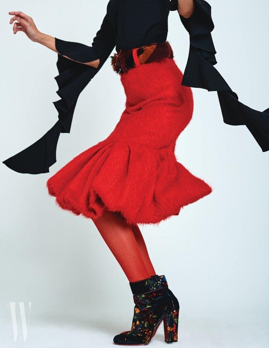 러플 장식이 멋진 검정 톱은 엘러리 by 네타포르테 제품. 80만원대. 빨강 스커트와 벨트는 프라다 제품. 슈즈는 1백70만원, 벨트는 가격 미정. 벨벳 소재 꽃무늬 슈즈는 크리스찬 루부탱 제품. 가격 미정.