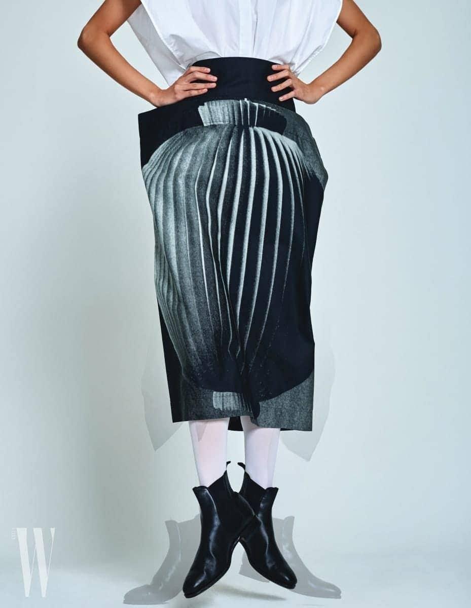 정물 사진이 프린트된 구조적인 형태의 스커트는 포츠 1961 제품. 가격 미정. 검은색 첼시 부츠는 카르미나 by 유니페어 제품. 29천원.