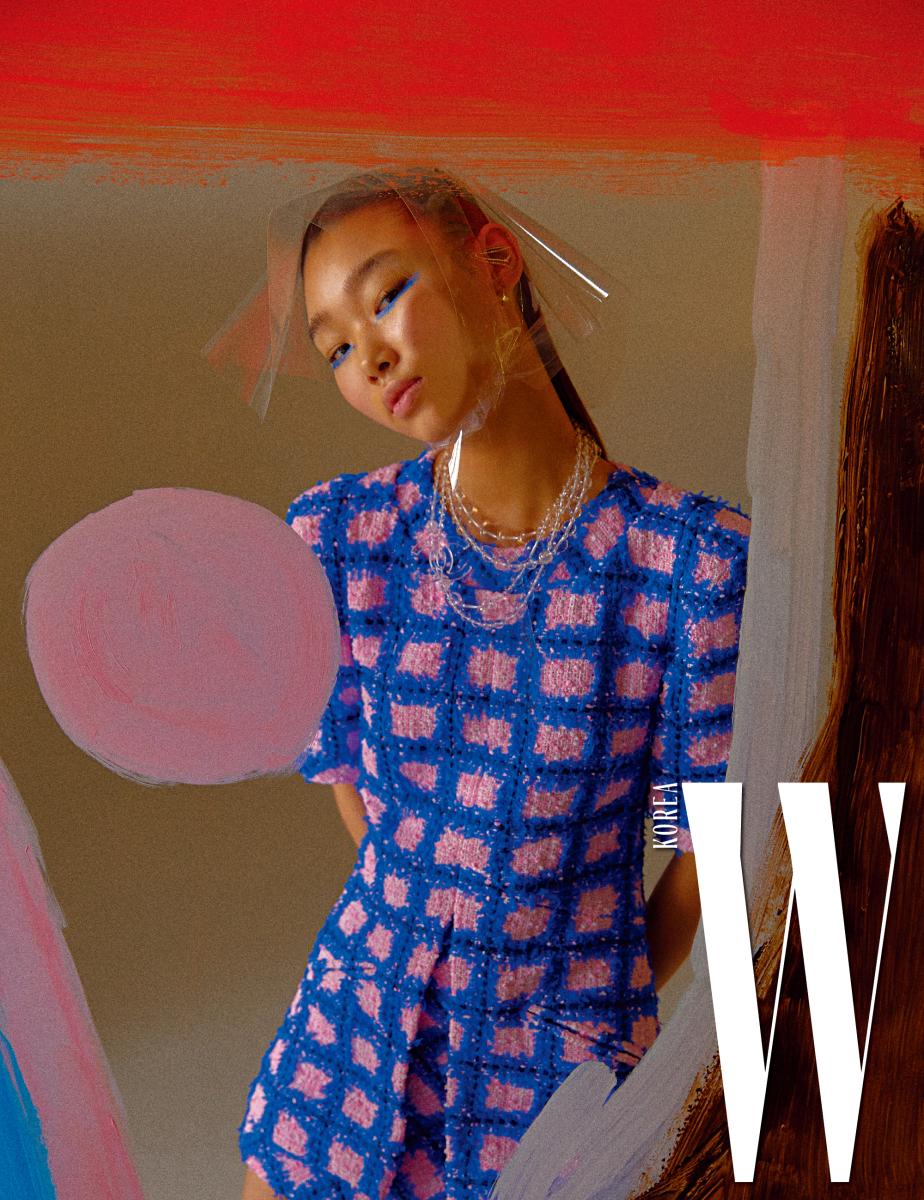 컬러 조합이 멋진 트위드 소재 체크 미니 드레스, 물방울을 연상시키는 투명한 구슬 목걸이는 Chanel 제품.