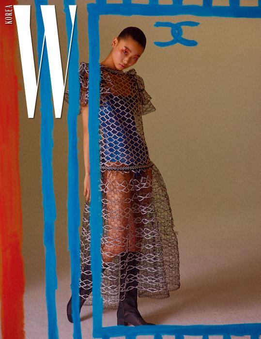 러플 장식의 섬세한 레이스 드레스, 안에 입은 파란색 수영복, 검정 부츠는 모두 Chanel 제품.
