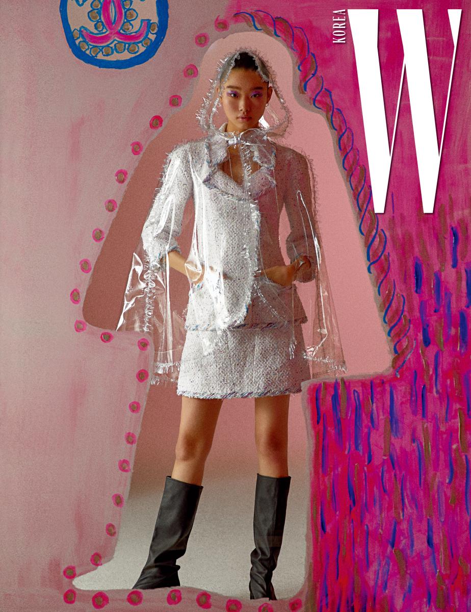 테두리에 컬러풀한 실로 포인트를 준 하얀색 트위드 재킷과 미니스커트, 리본 장식 비닐 케이프, 검은색 부츠는 모두 Chanel 제품.