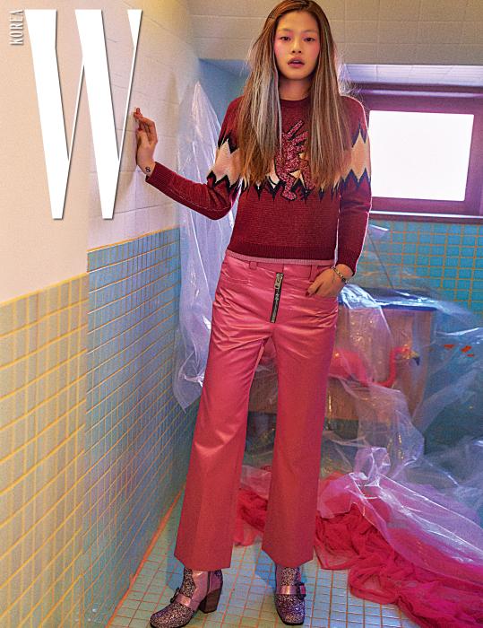 유머러스한 문양의 스웨터, 지퍼 장식 팬츠, 핑크 글리터 부티, 팔찌는 모두 Coach 제품.