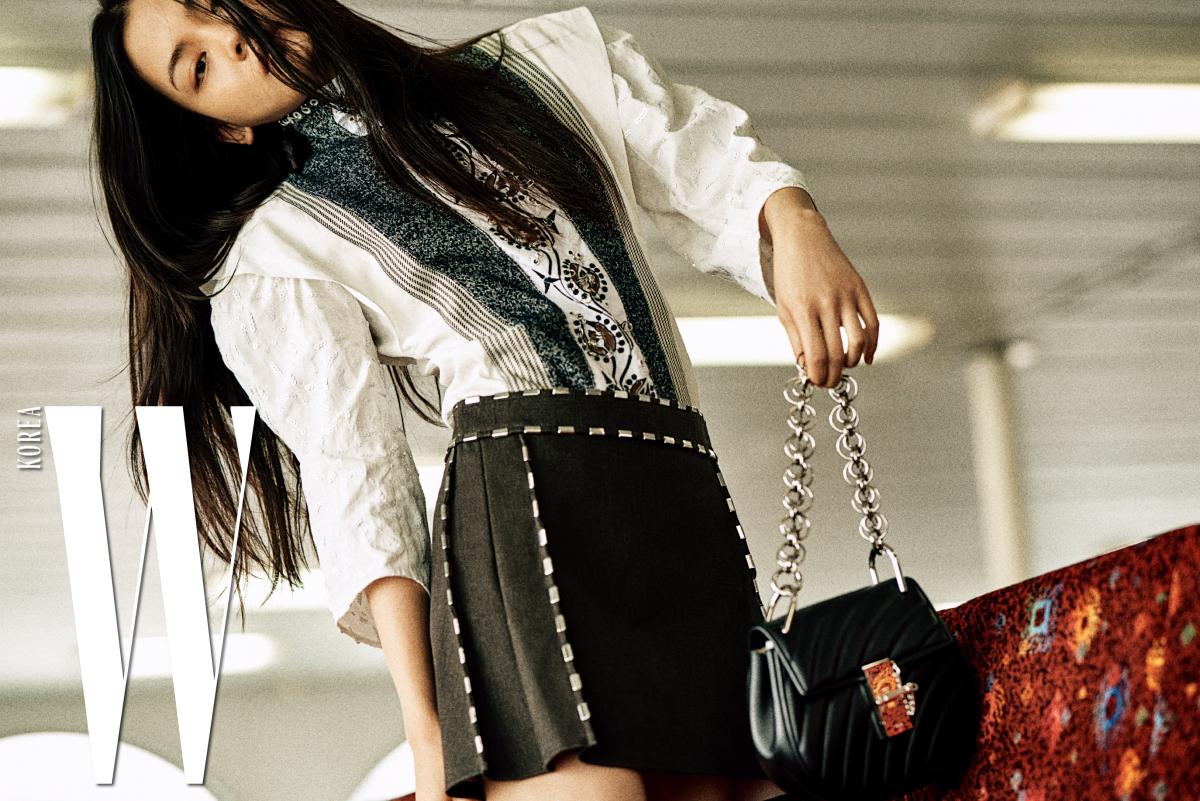 빅토리언 무드의 톱, 메탈릭한 장식이 달린 미니스커트, 검은색 드류 비즈 백은 Chloe 제품.