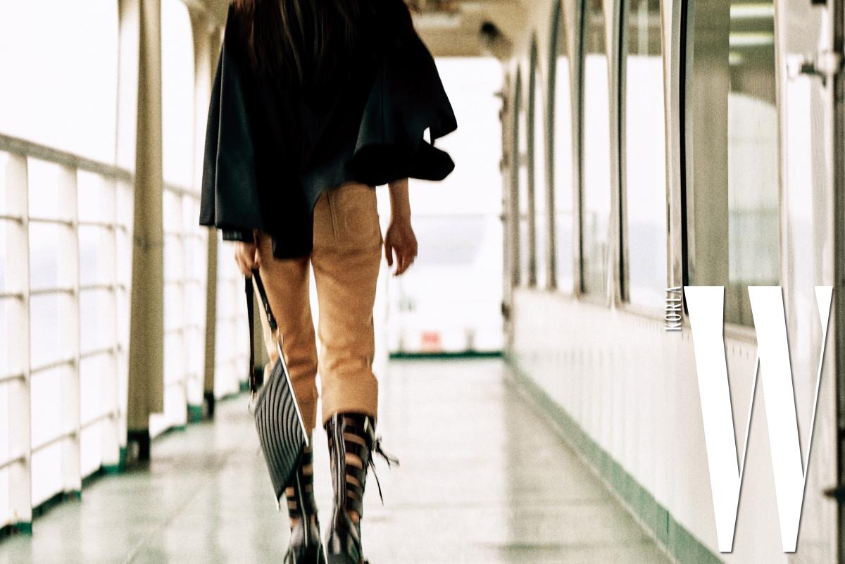 흰색 자수 톱, 망토가 달린 베스트, 주머니 장식 하이웨이스트 팬츠, 메탈 바 장식의 로이 백, 레이스업 장식의 라일리 부츠는 모두 Chloe 제품.