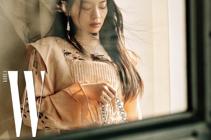 피어싱이 달린 하이넥 톱, 살구색 쇼츠, 은색 체인의 드류 비즈 백은 Chloe 제품.