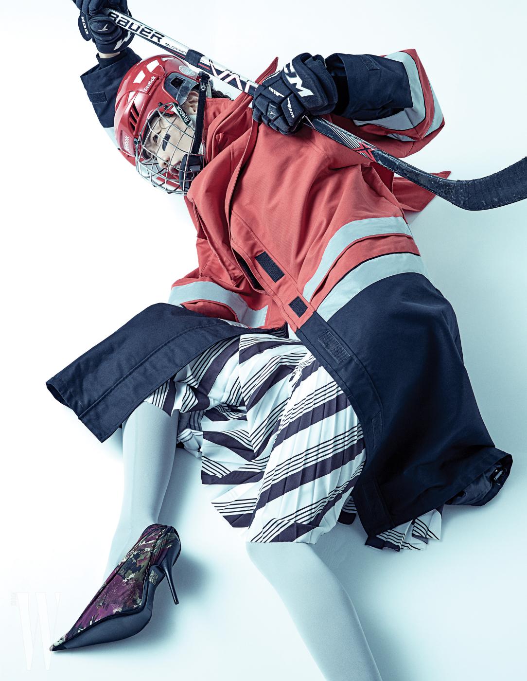 리플렉티브 소재를 더한 롱 재킷과 줄무늬 패턴 스커트, 회색 타이츠, 여러 컬러가 뒤섞인 슈즈는 모두 발렌시아가 제품. 재킷은 4백만원대, 스커트는 2백50만원대, 타이츠와 슈즈는 가격 미정. 아이스하키 헬멧, 장갑, 스틱은 '드래곤 아이스하키팀' 협찬 제품.