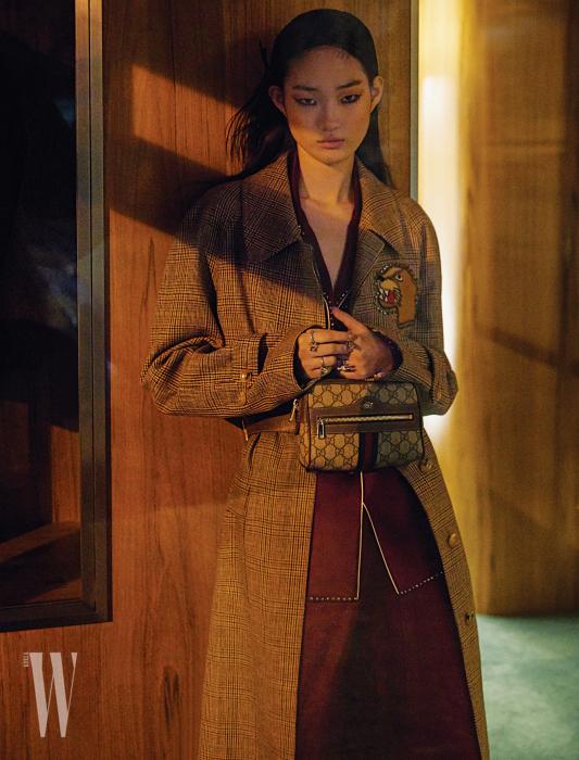 체크무늬 코트, 실크 파자마 셔츠와 팬츠, 허리에 착용한 가방과 반지들은 모두 Gucci 제품.