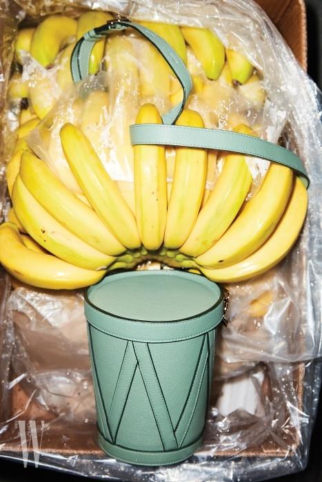 바나나 상자에 들어 있는 에메랄드그린 컬러의 둥근 박스 백은 니나리치 제품.