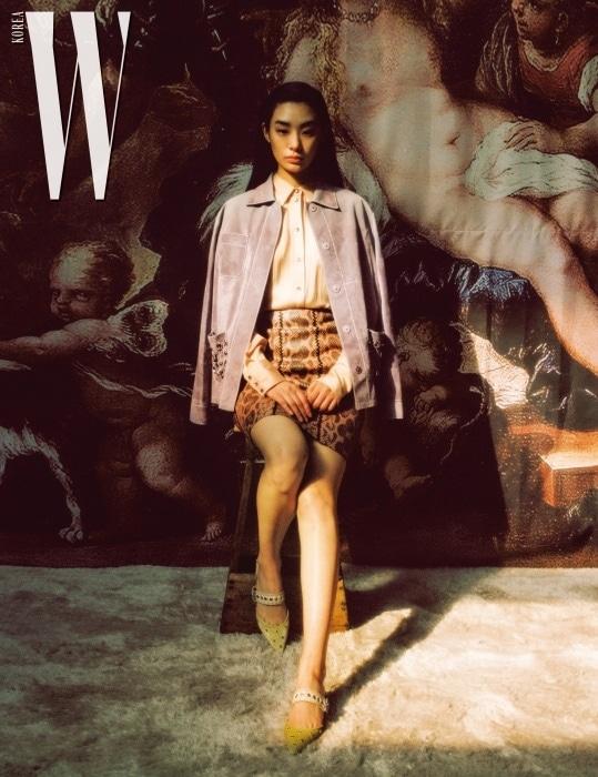 화려한 장식을 더한 라일락 색상의 재킷, 피치 색상의 실크 블라우스, 파이톤 소재 A라인 스커트, 메탈 장식의 플랫 메리제인 슈즈는 모두 Bottega Veneta 제품.