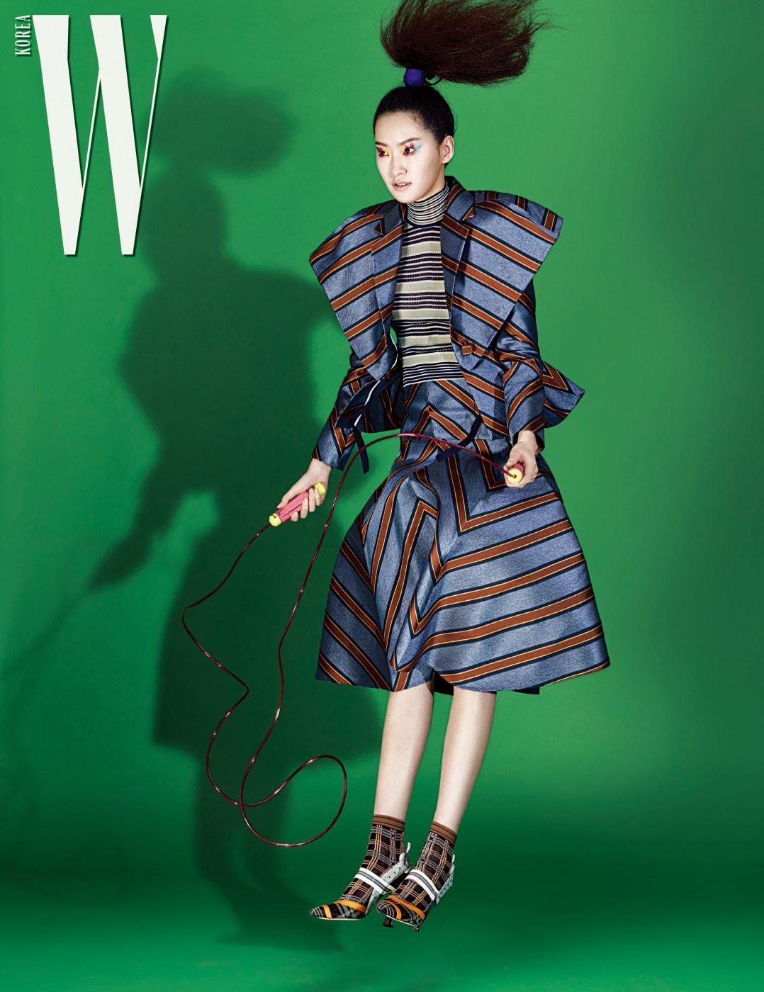 구조적인 어깨 라인이 특징인 줄무늬 재킷, 니트 톱, 풍성한 스커트, 체크무늬 양말과 스포티한 슈즈는 모두 Fendi 제품.