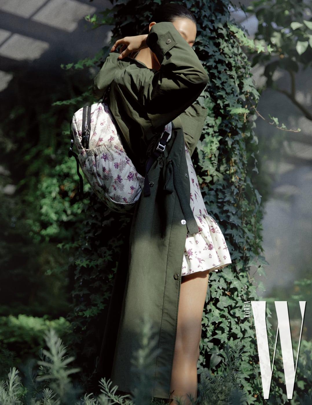 로맨틱한 색감의 꽃무늬 원피스와 백팩, 볼륨감 있는 카키 롱 점퍼는 모두 Moncler 제품.